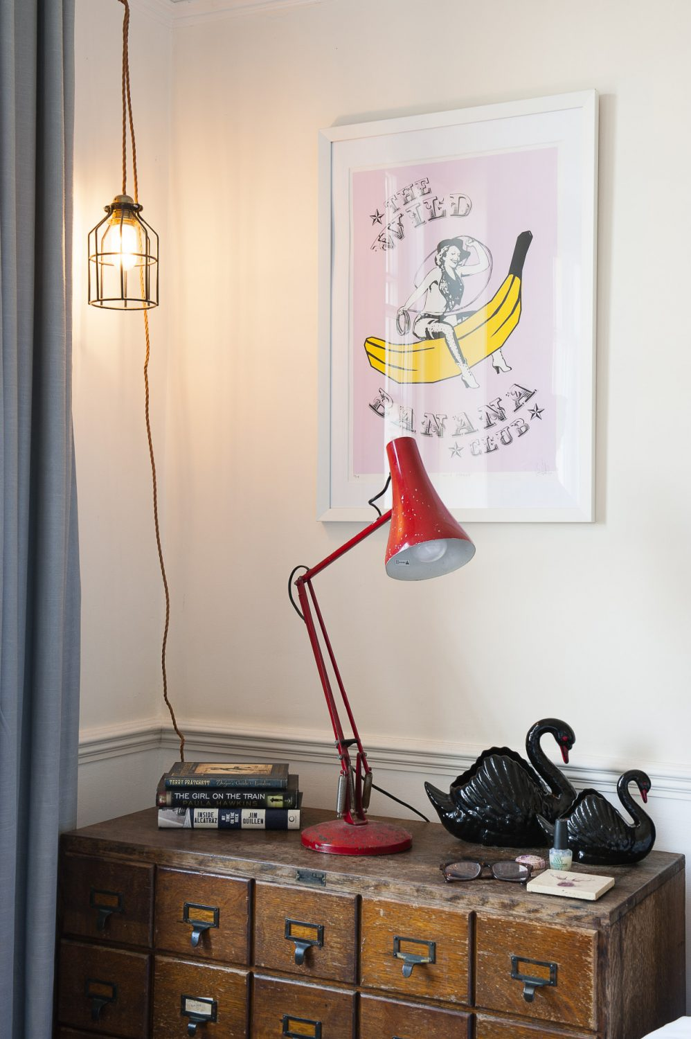 A red Anglepoise lamp sits on top of a chest made from card index drawers that Stuart and Sarah found in Hastings Old Town. They have collected the swans from boot fairs and vintage shops over several years. The pendant light is from Dyke & Dean. The 'Wild Banana Club' print is by their friend Ben Allen