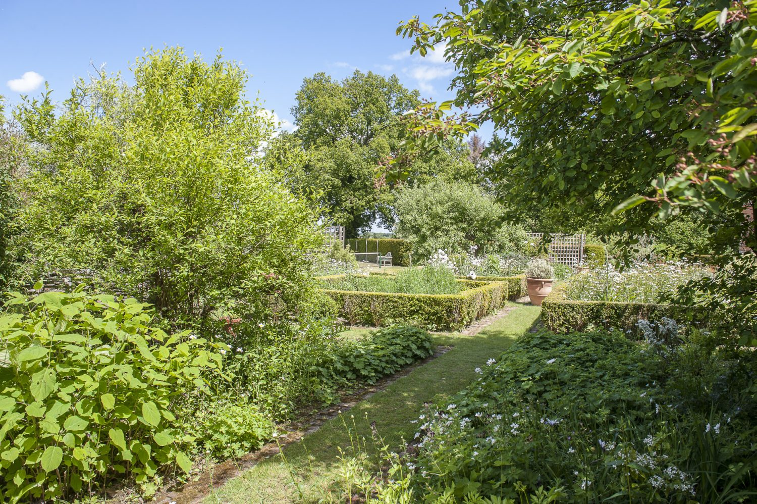 Throughout the garden blousy borders appear to blend seamlessly into glorious open countryside