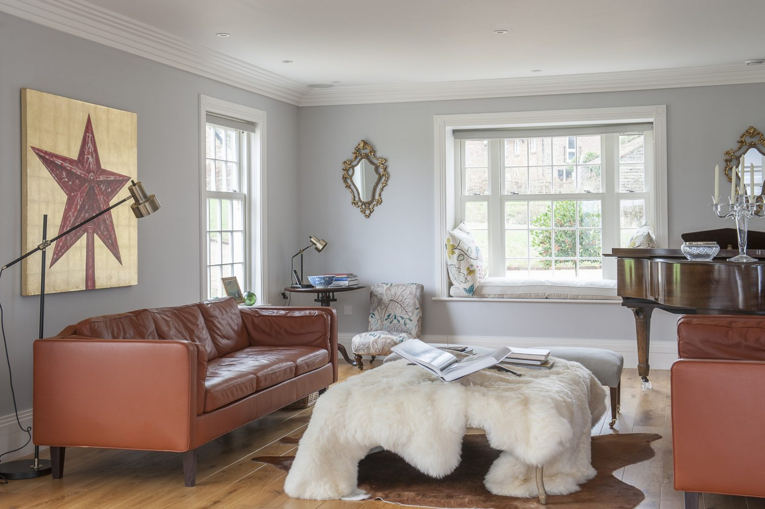 The opposite end of the living room-cum-drawing room has a different feel; perhaps more 'rustic modern', with luxurious sheepskins and retro leather sofas