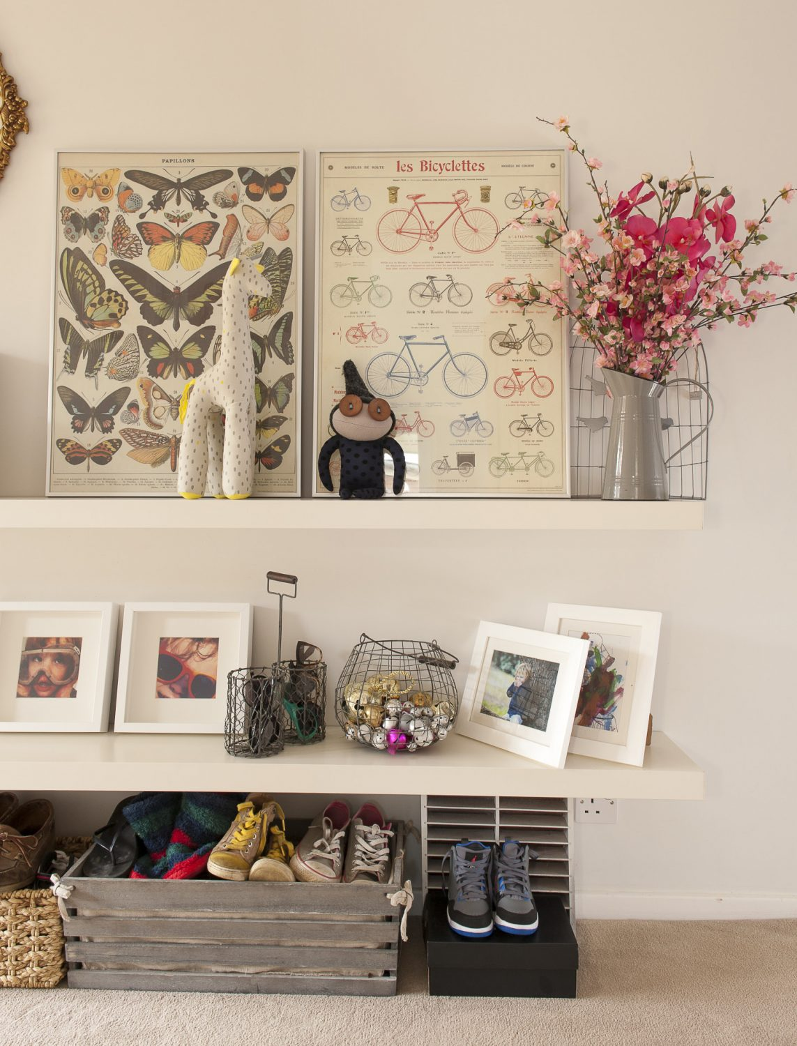 Shelves in the hallway are filled with family photographs and large framed prints, whilst underneath shoes are kept neatly ordered in a row of wooden crates and baskets