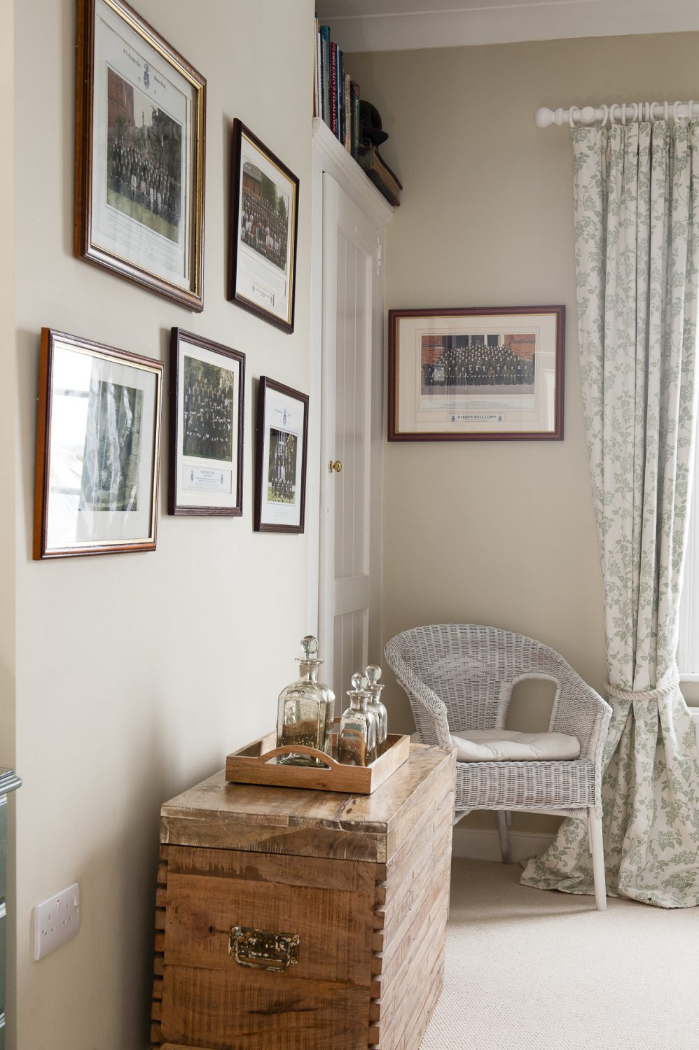 Pictures hang on the wall above a wooden chest