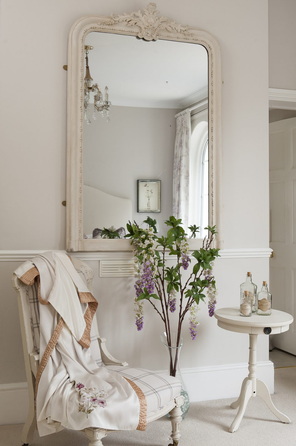 A large mirror, chair and occasional table