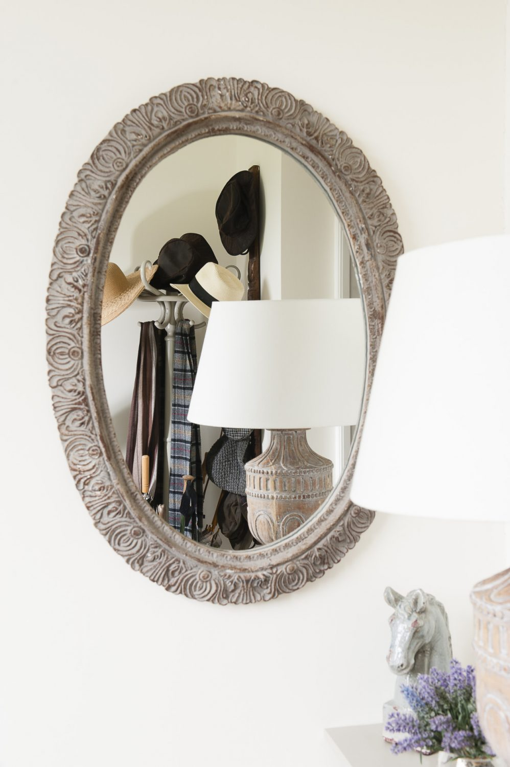 An large oval mirror in the hallway
