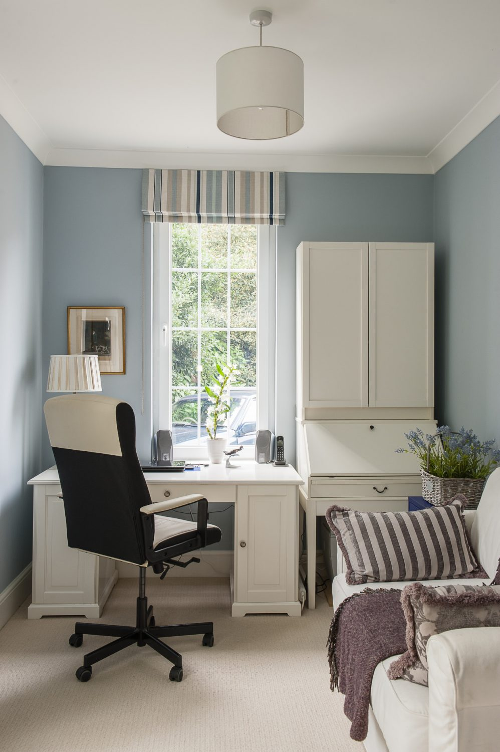 The study is painted in a cool blue and furnished simply with white painted bureau and desk
