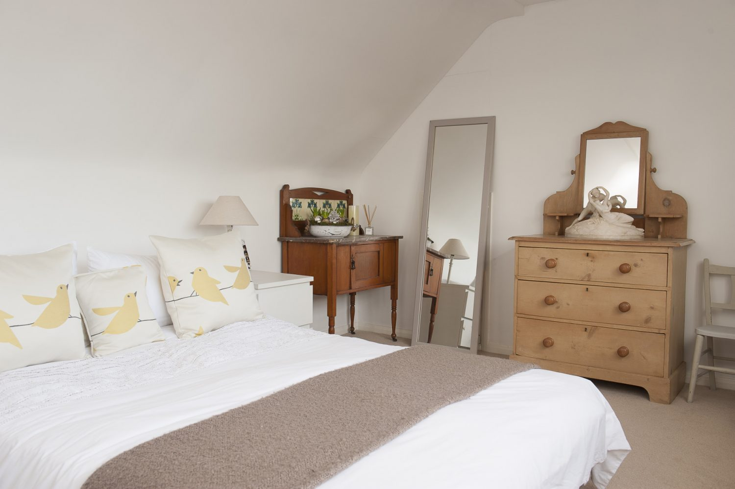 Next to the sitting room, a discreet staircase leads up to a pretty, vaulted guest bedroom