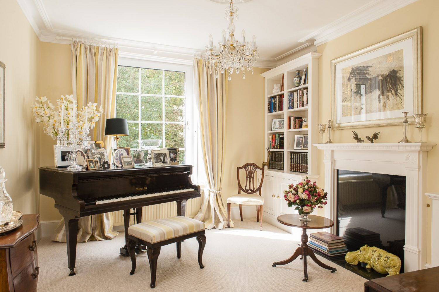 The music room walls are painted in Farrow & Ball's Cream. Pride of place is given to the ebony Challen baby grand piano that belonged to Murielle's mother.
