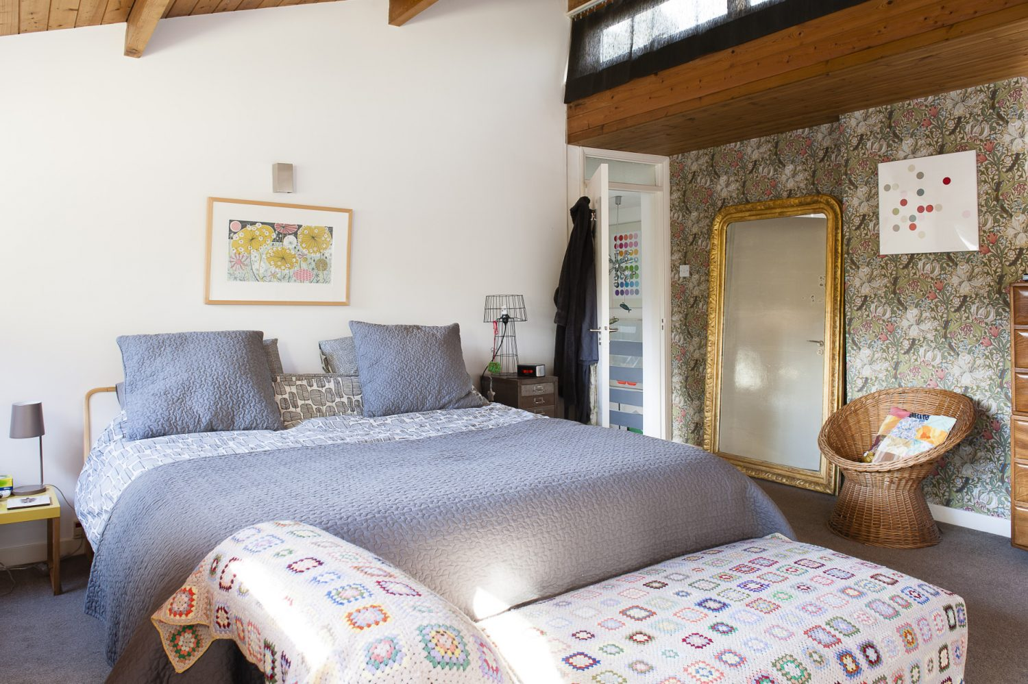 The master bedroom was once virtually all pine, three walls and soaring pitched ceiling. Sam covered one wall in a William Morris print, leaving the ceiling bare