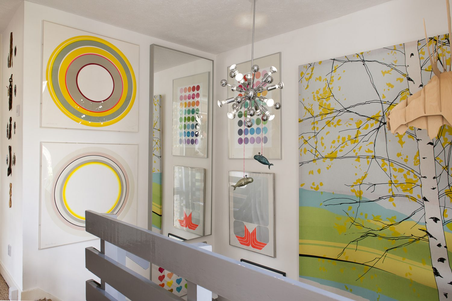 Two sizable canvases depicting large neon circles by Sam's favourite artist, Sophie Smallhorn, hang to the left of the landing