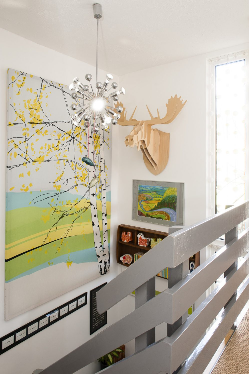 Halfway up the stairs hangs a truly vast canvas of silver birches from Skandium and a Banksy limited edition