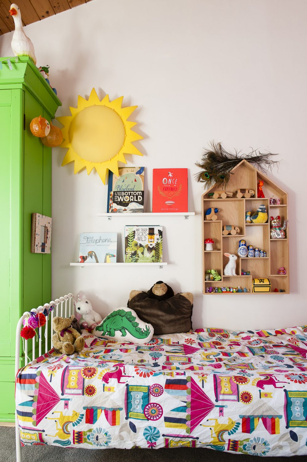 Daughter Esther's room sports the same dramatic pitched pine ceiling as her parents'. Her wardrobe started life a plain pine but is now a bright pea green. Books and ornaments are kept neatly ordered on floating shelving