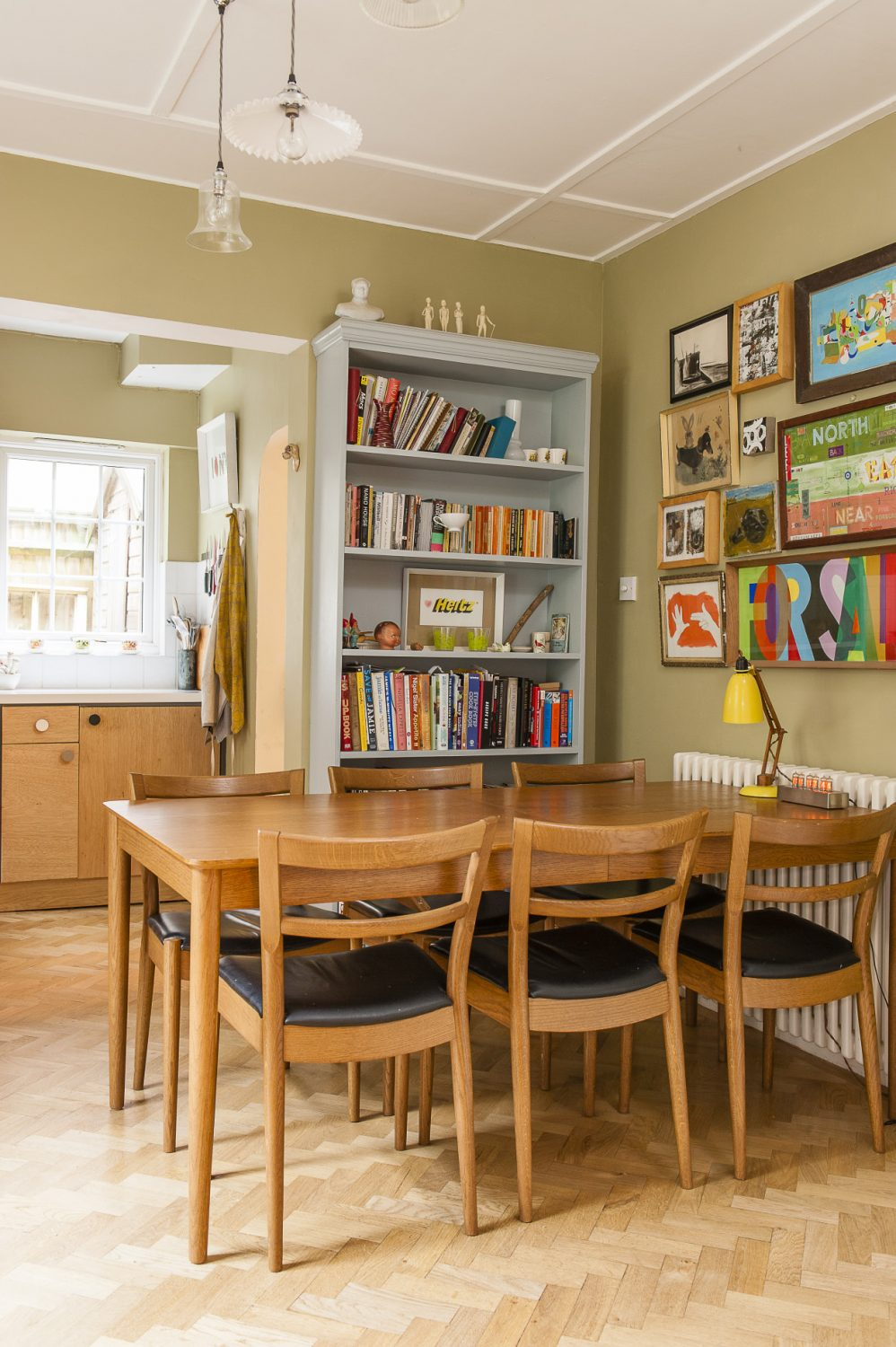 Glass shaded lights from Baileys Home illuminate the elegant retro Ikea table in the dining area. On the wall above the table is a collection of favourite paintings