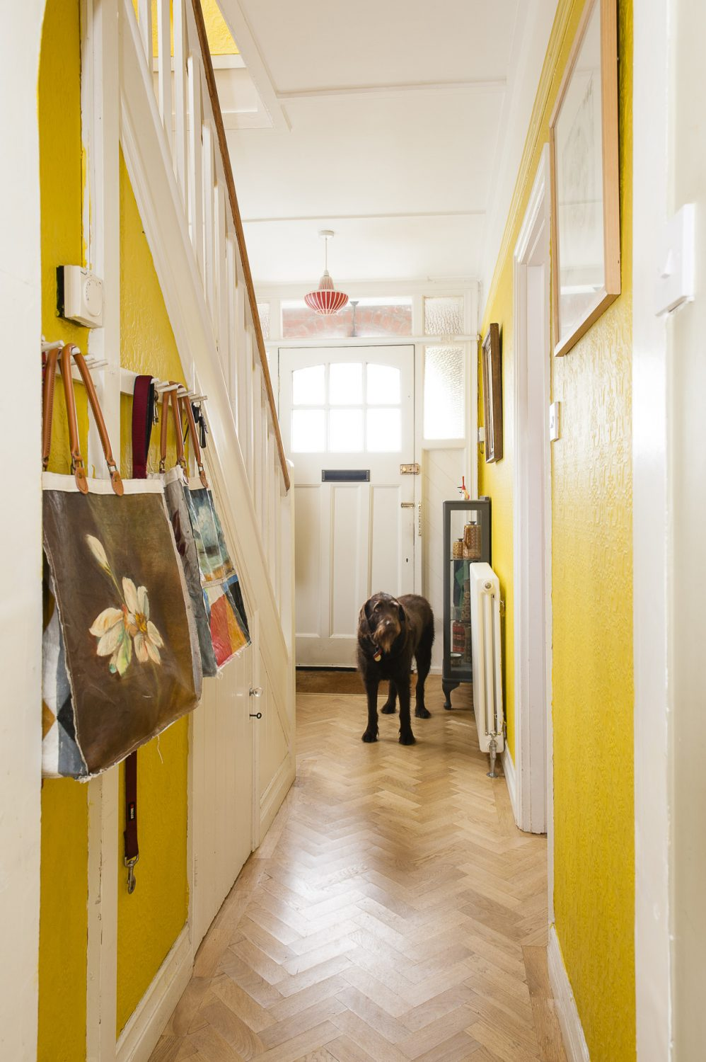 Hand-painted canvas bags from John and Anna's latest project hang from hooks in the hallway