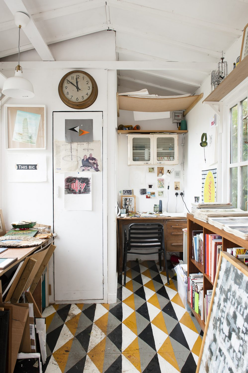 John ensured that the studio was constructed from as much reclaimed material as possible. The wooden floors have been hand-painted with a geometric pattern and the walls and desktops are flooded with inspiring finds