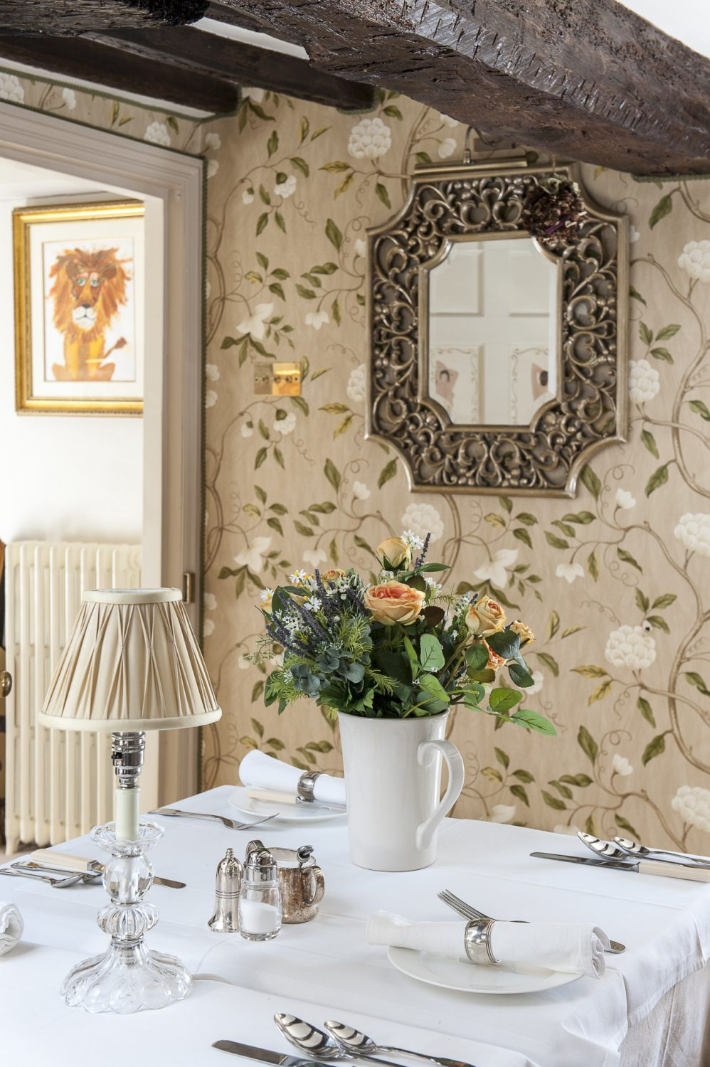 The dining room is used principally as a breakfast room. Nina has varnished the Colefax & Fowler 'Snowtree' wallpaper to give it the appearance of silk