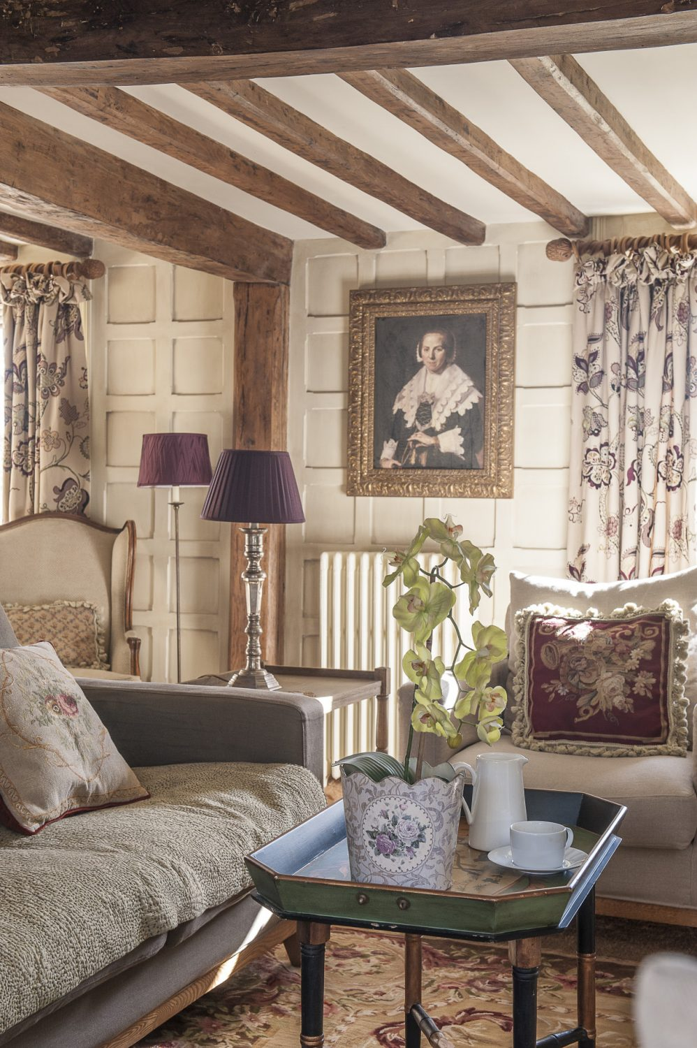 In the drawing room heavily embroidered Sanderson curtains complement the Elizabethan panelling