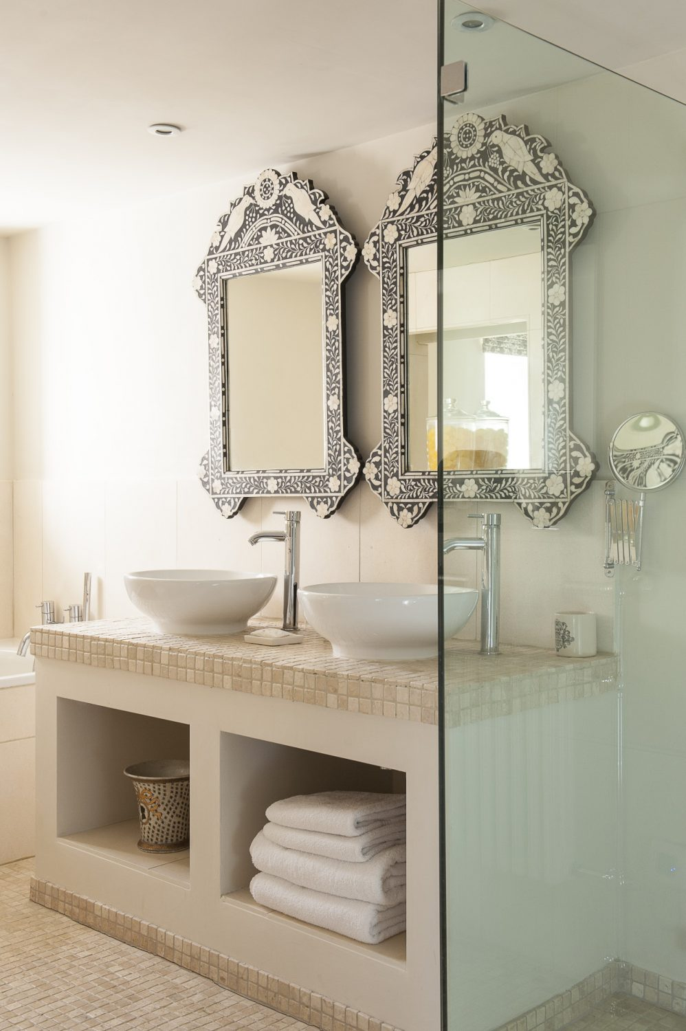 A pair of Moorish mirrors are a striking feature of Keynes's limestone en suite, complete with a deep bath and glass-walled wet-room shower