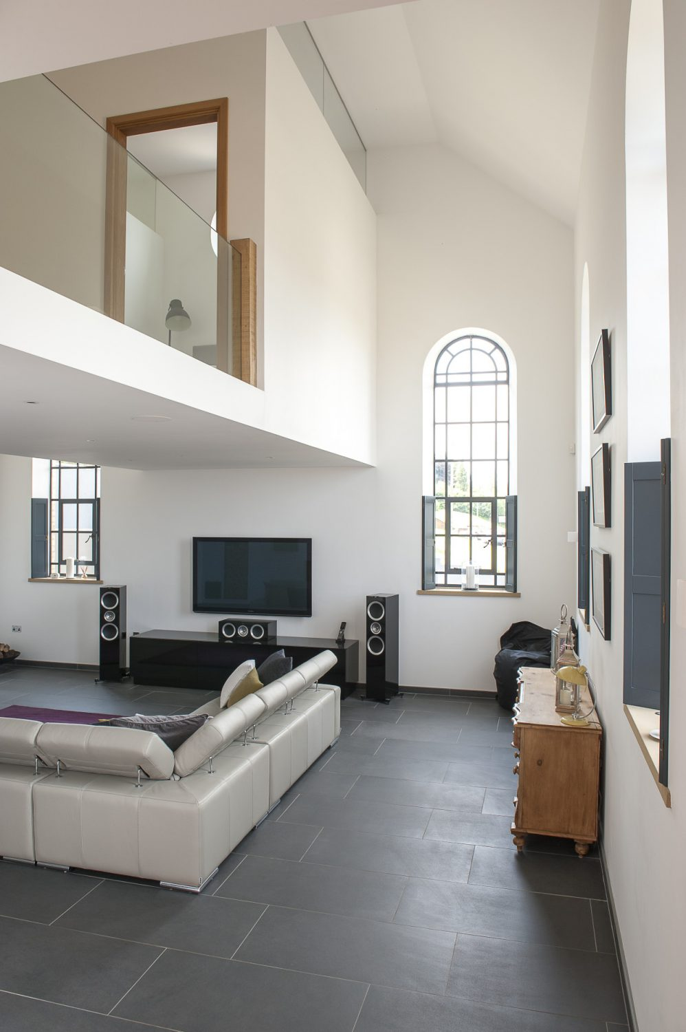 Nick and Sonja were determined to keep the chapel windows as single entities. In order to do this, they divided the living room into three spaces, two soaring to the height of the windows at either end of the room and a centre section with a lower ceiling which provides for second floor accommodation