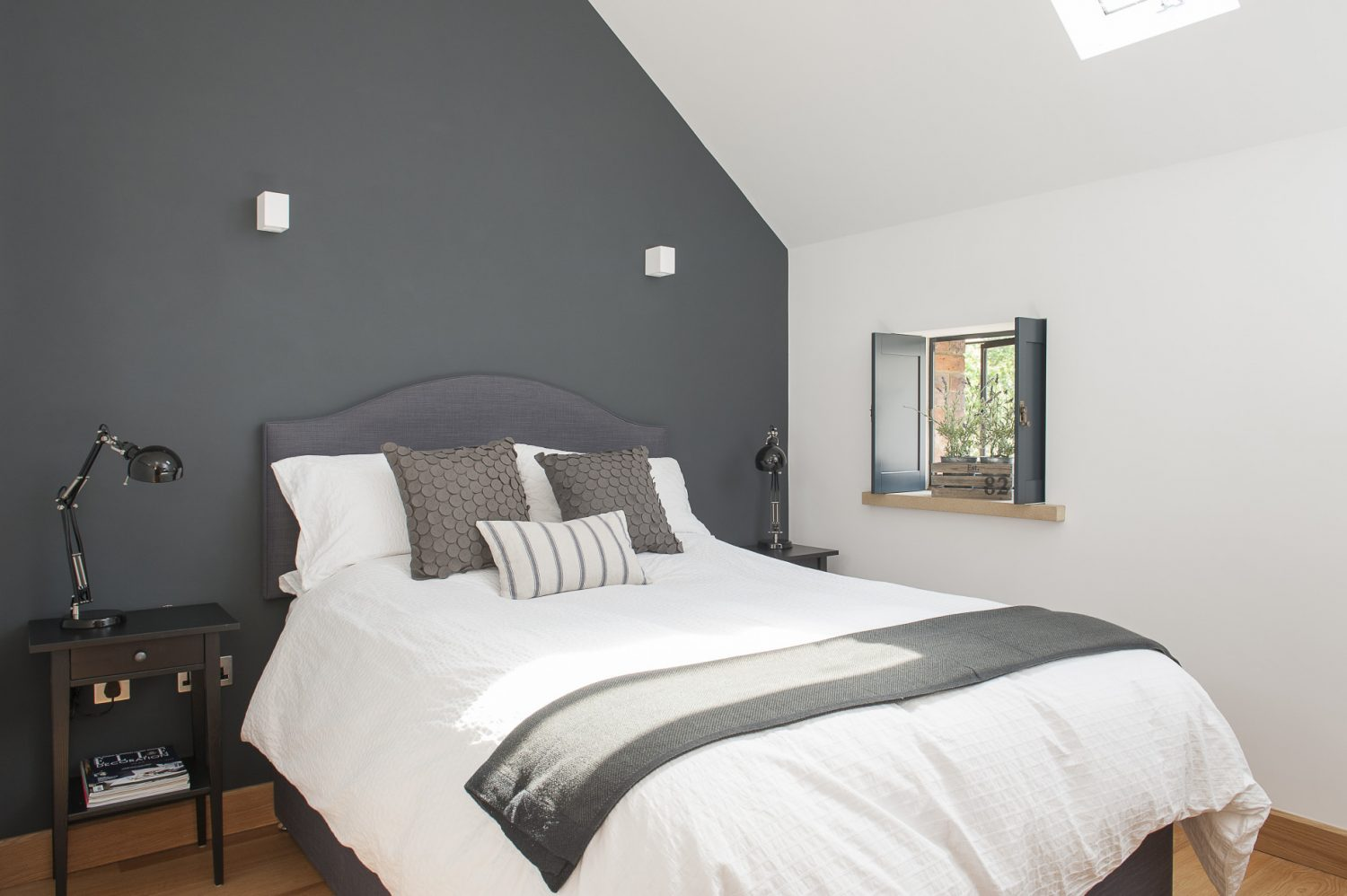 The second guest room, painted a deep grey, is a pleasing combination of contemporary minimalism with a dash of country charm – the latter provided by a pretty shuttered window