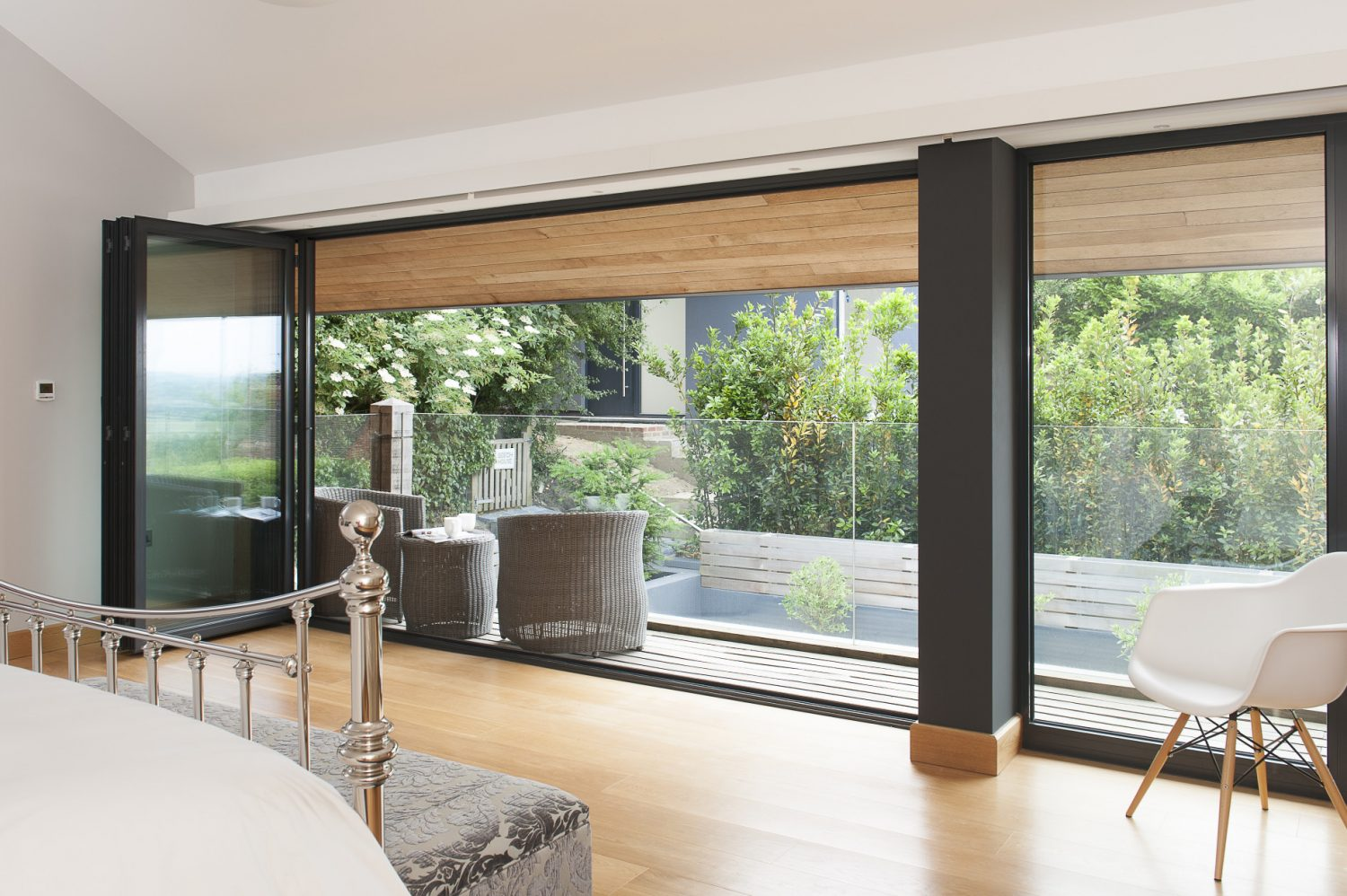 The wall of bi-folding doors is echoed upstairs in the master bedroom directly above the kitchen where they open out onto a decked balcony and more Lloyd Loom surrounded by a plate glass balustrade