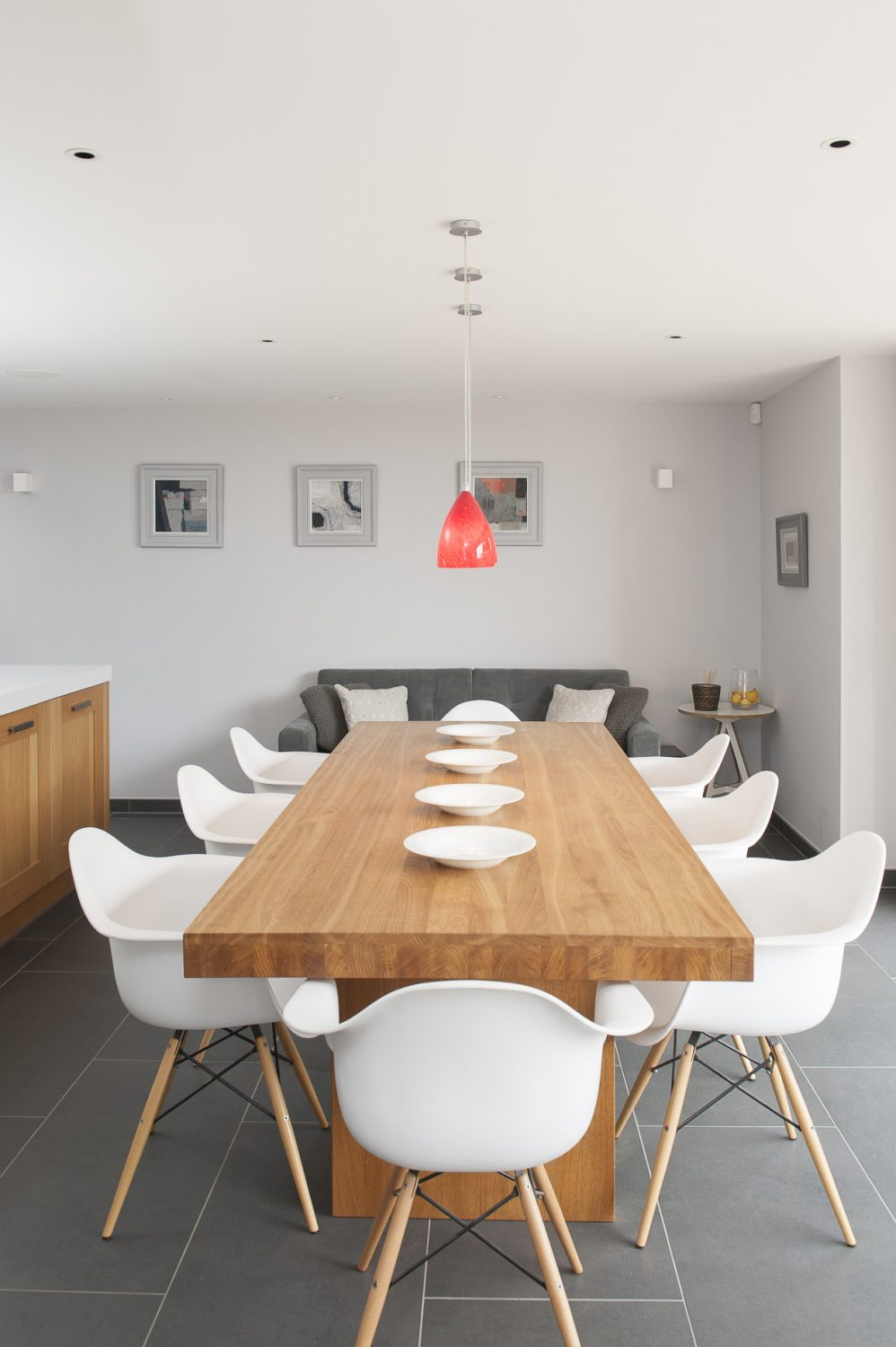 In the kitchen bi-folding doors lead out onto an elegant sandstone terrace and its Lloyd Loom table and chairs. The units and surfaces and island are courtesy of Cambridge Kitchens, the dining table and Eames-style chairs are from John Lewis