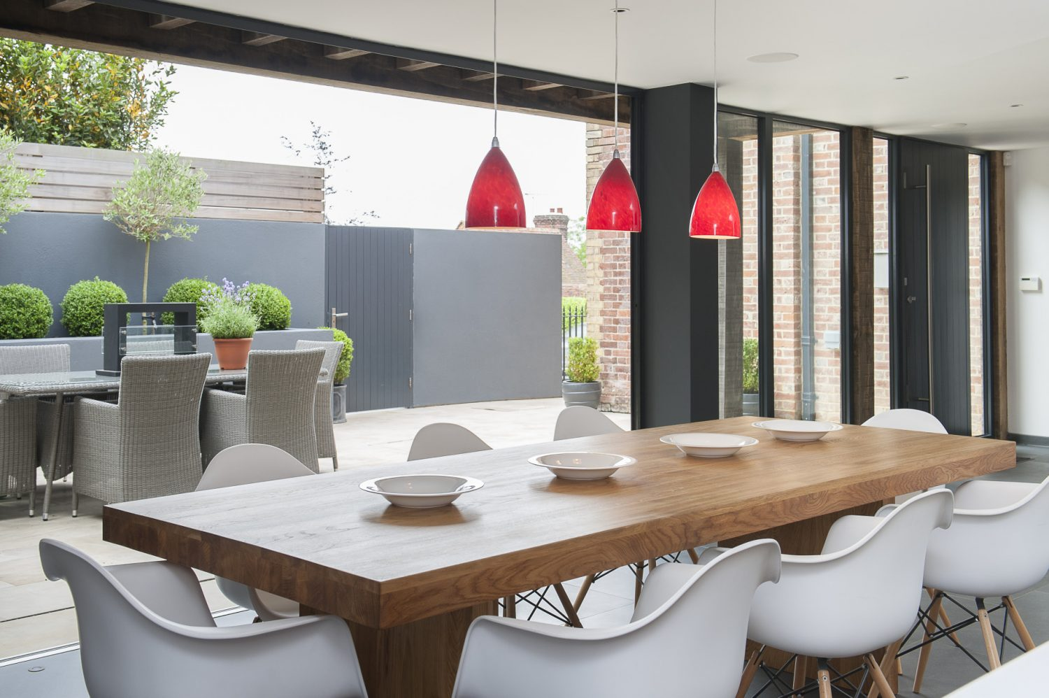 In the kitchen bi-folding doors lead out onto an elegant sandstone terrace and its Lloyd Loom table and chairs