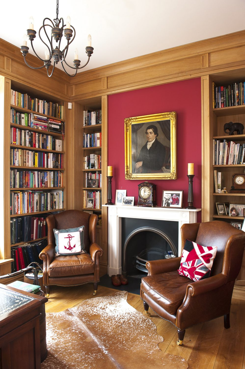 The study is painted in Farrow & Ball Chinese Red, a striking colour that really works and is the perfect backdrop for the oak bookcases