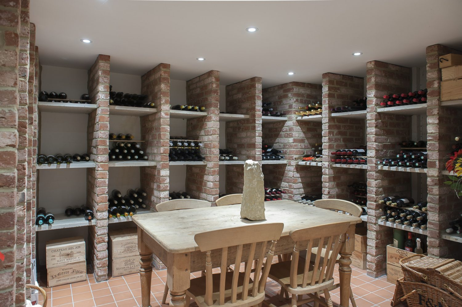 Tucked away down a discreet staircase at the back of the house, there is every wine-lover's dream; a vast, cool cellar built from brick and stone, where Julian keeps a prized collection of wine. A rustic table is the perfect spot for Julian and fellow wine-lovers to sample favourite wines