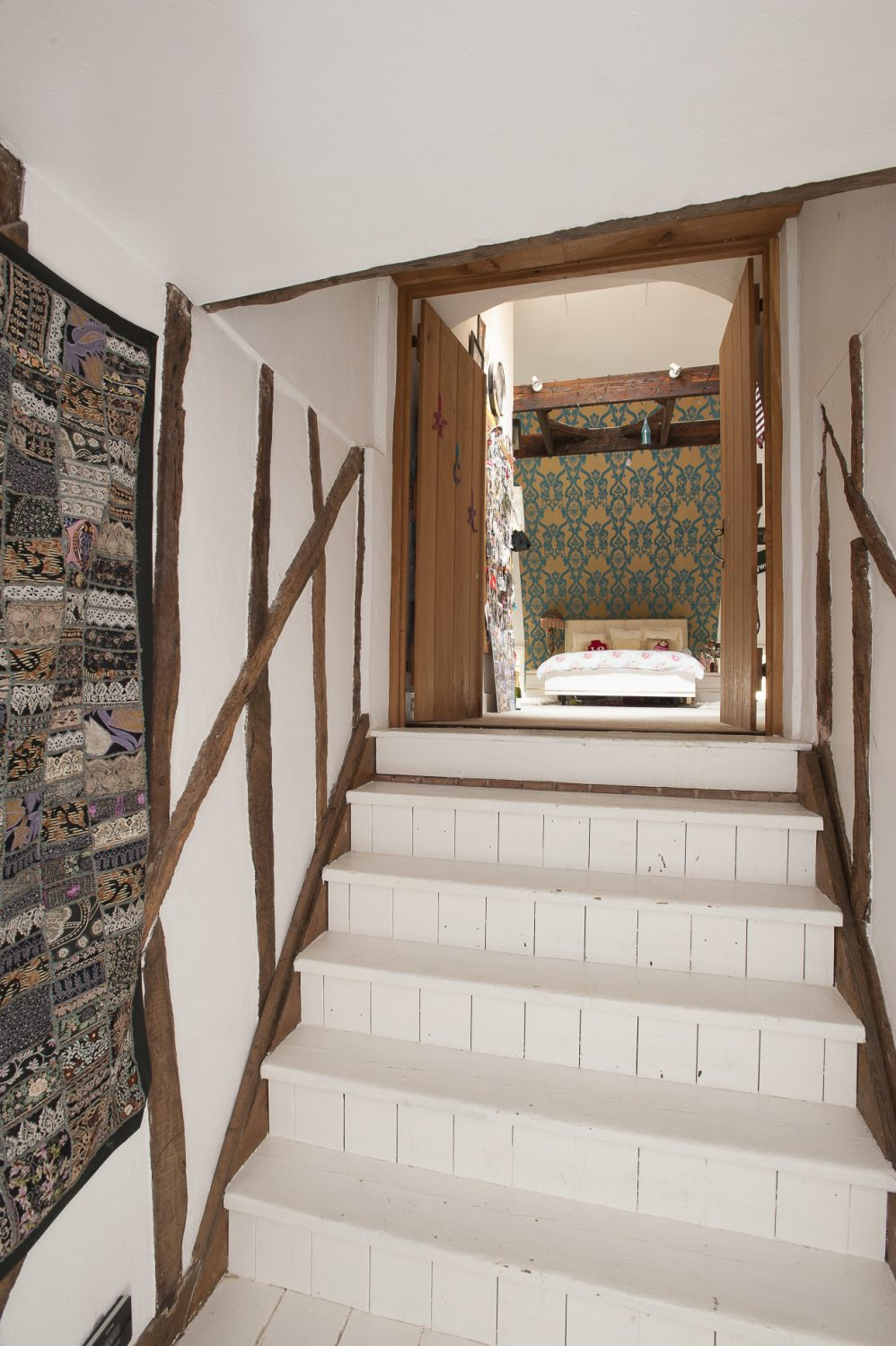 Up a pretty white painted staircase to the second floor is daughter Holly's room