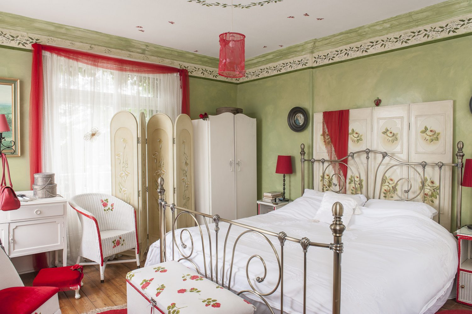 Mick and Carmel's room is a bright and airy retreat. Accents of olive green and red, combined with Carmel's stencils, work together to create a rather Mediterranean feel