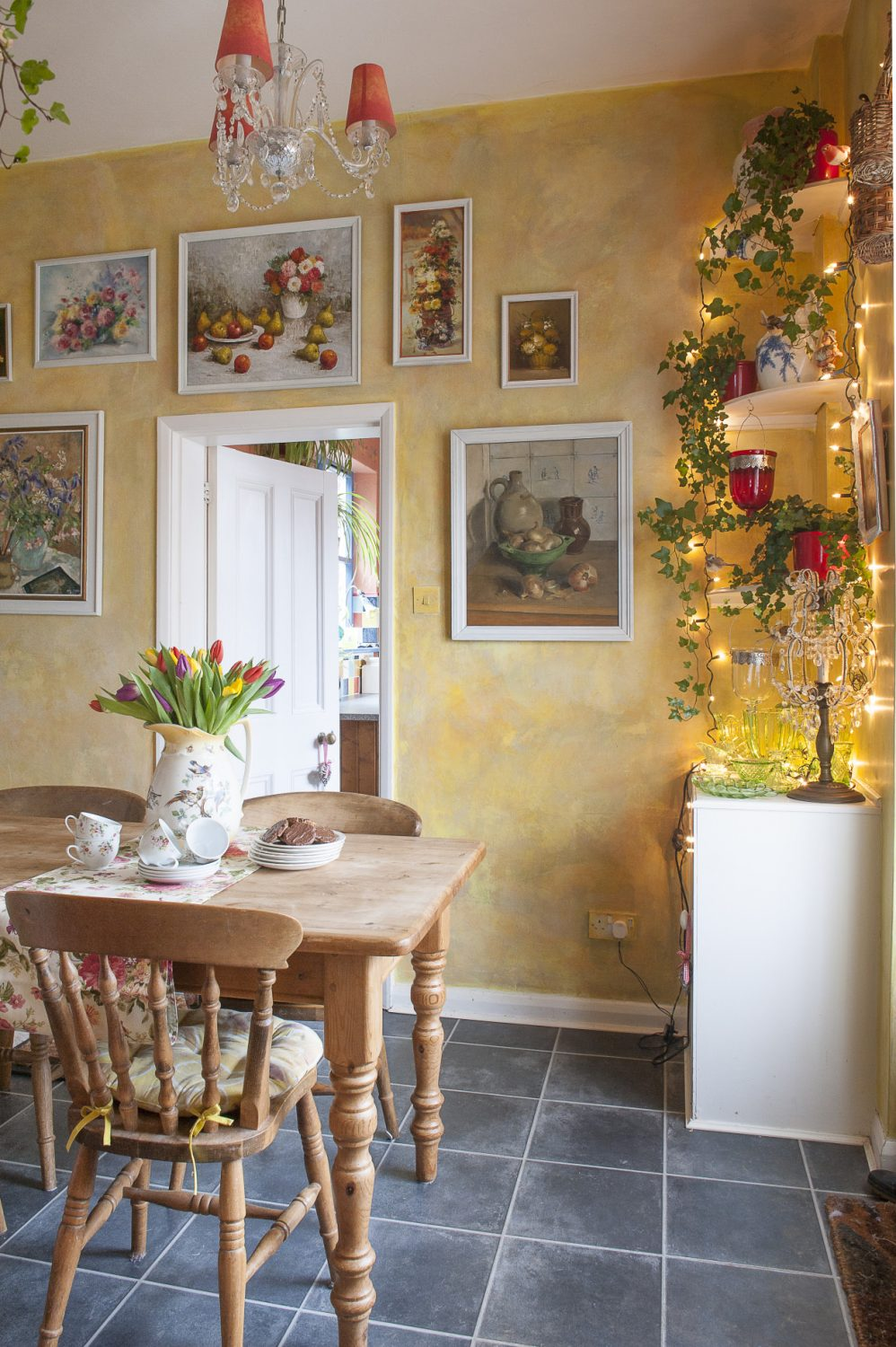 The yellow breakfast room is covered in still life pictures and cascades of ivy