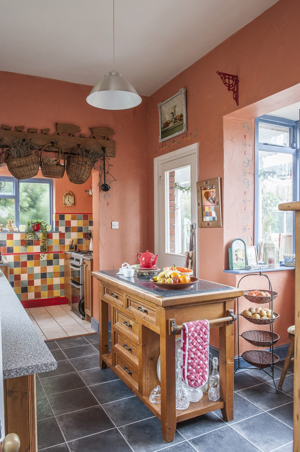 The kitchen is painted and tiled in a Spanish palette of rich terracotta and sunshine yellow