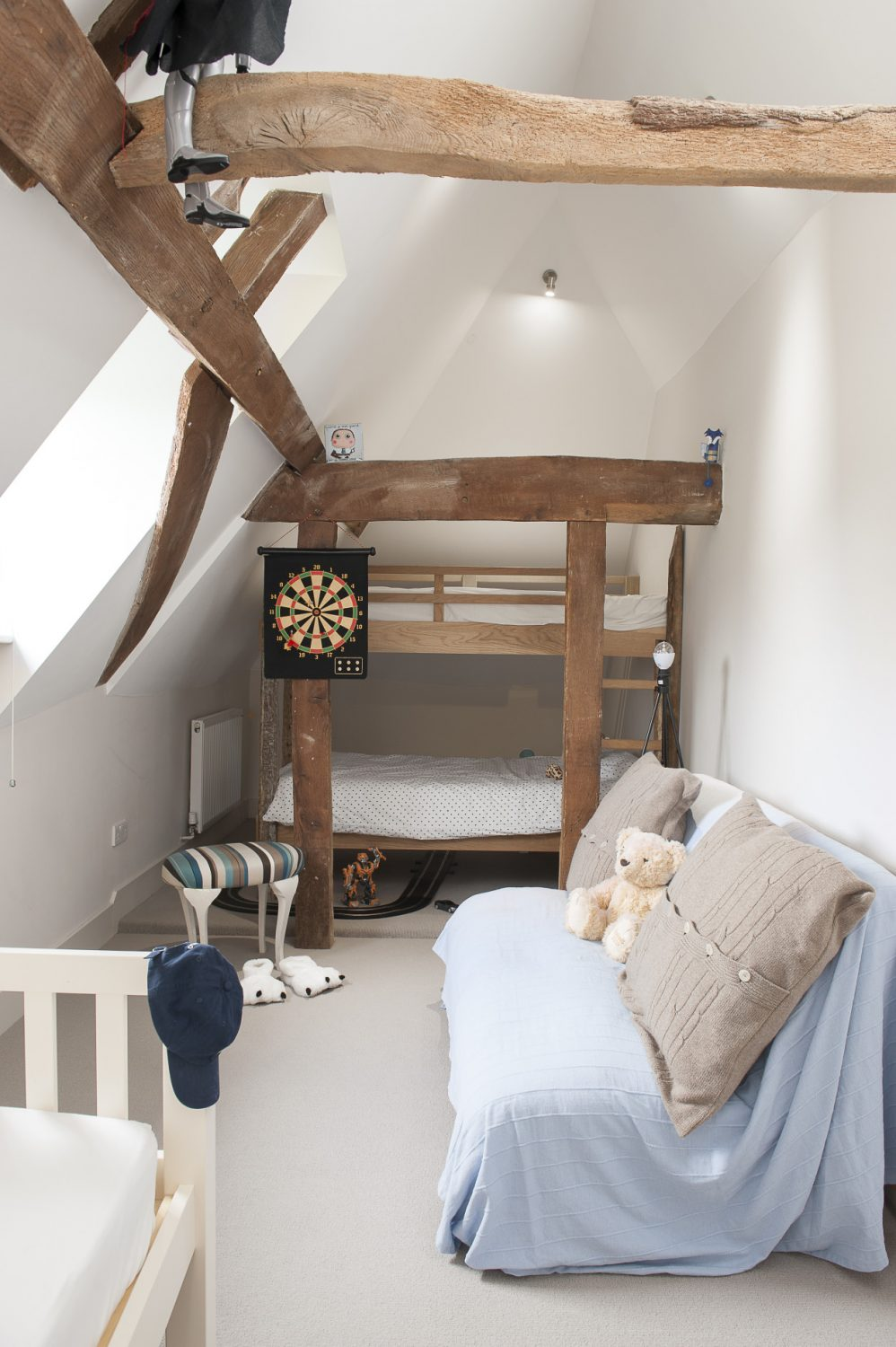 The children's attic bedrooms, with bunks designed by Perrine and built by Jason, are like an enchanted vaulted and beamed eyrie