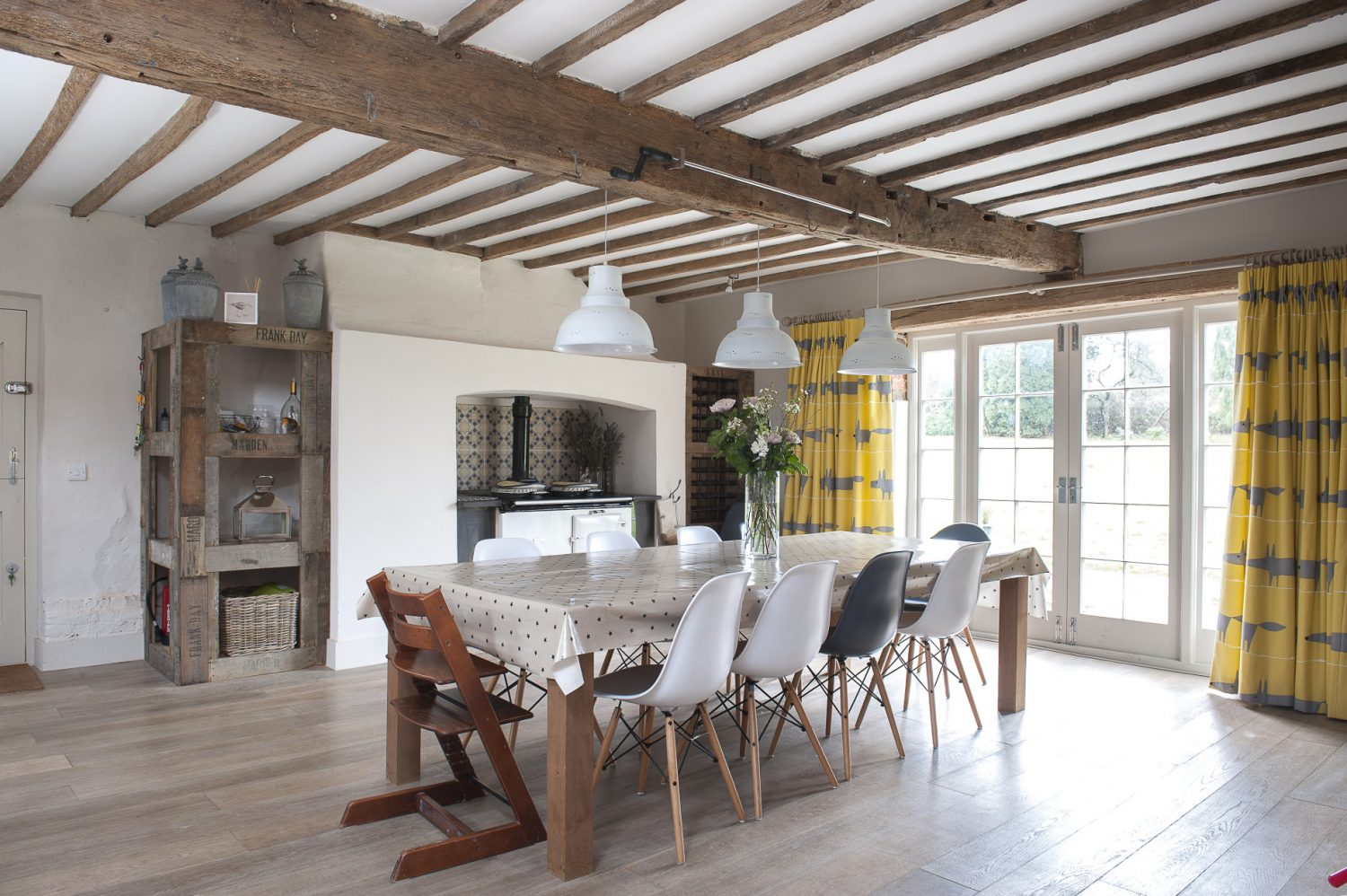The ten-seater kitchen-cum-dining table was designed by Perrine and made by their carpenter Jason Tanner. Alongside is the Aga, with geometric tiles behind, and a shelving unit made from reclaimed local fruit bins