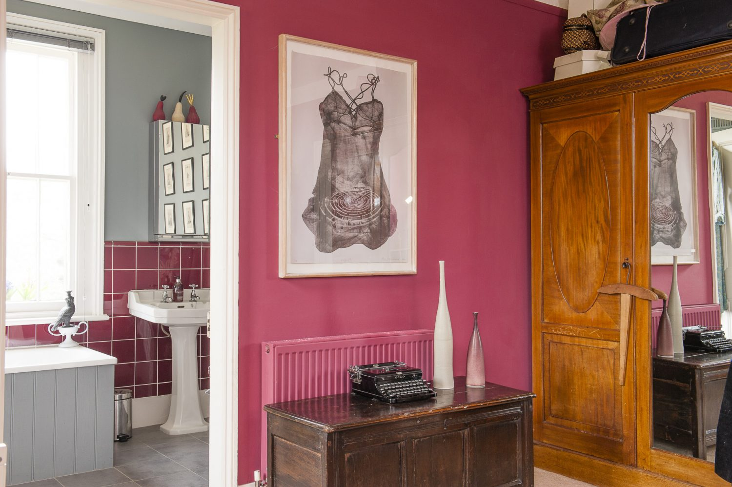 The spare bedroom is painted a juicy raspberry red, the bed covered with a boiled felt throw