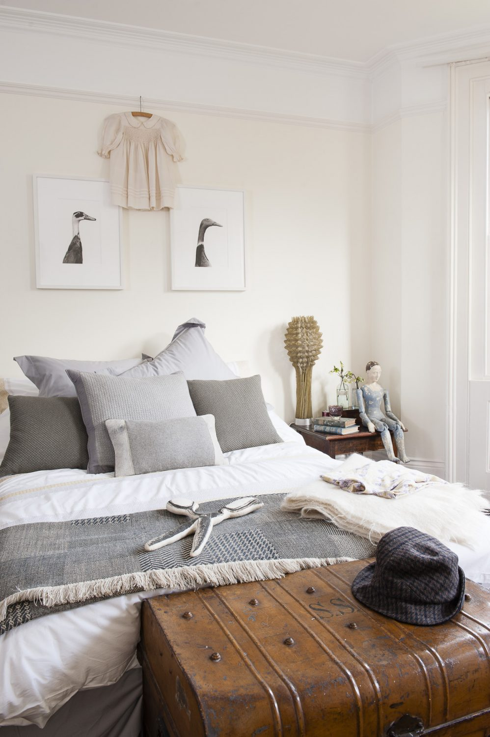 A pair of beautifully illustrated Indian Runner ducks are mounted above the bed in the master bedroom, fitting in perfectly with the room's cool greys and crisp whites