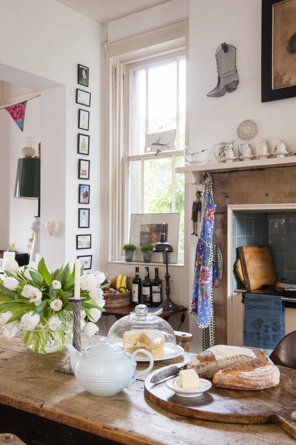 Freshly baked bread and cake make a welcoming sight on the kitchen table. Ceramics by Kate Schuricht, Sue Binns, Andre Wicks and Stuart Houghton line the mantelpiece