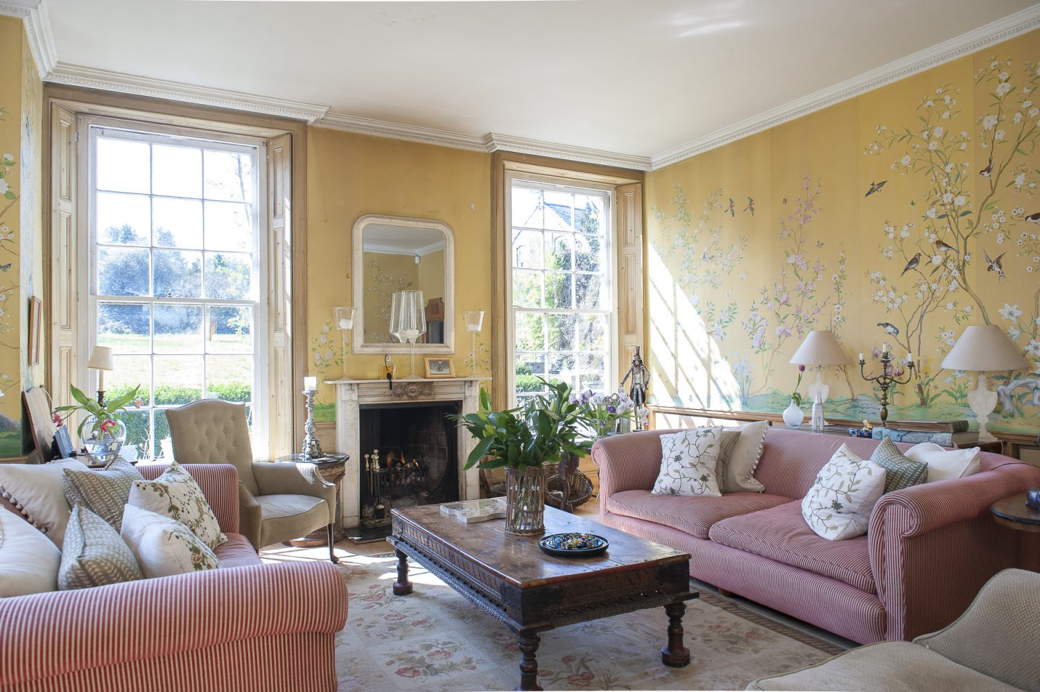 The drawing room, with its open fire and huge sash windows, overlooks the lawn and mature gardens. Christel has had the Conran sofas for many years, while the Indian 'elephant table' belonged to Lord Cowdrey and came from Bangalore. Josef Holst painted the Chinese-style murals