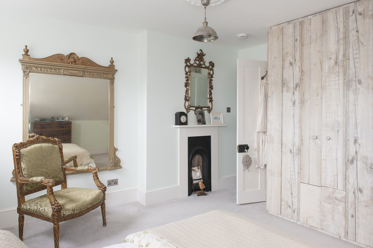 Louise has created a clever visual trick by choosing wood effect wallpaper to cover the built-in wardrobe