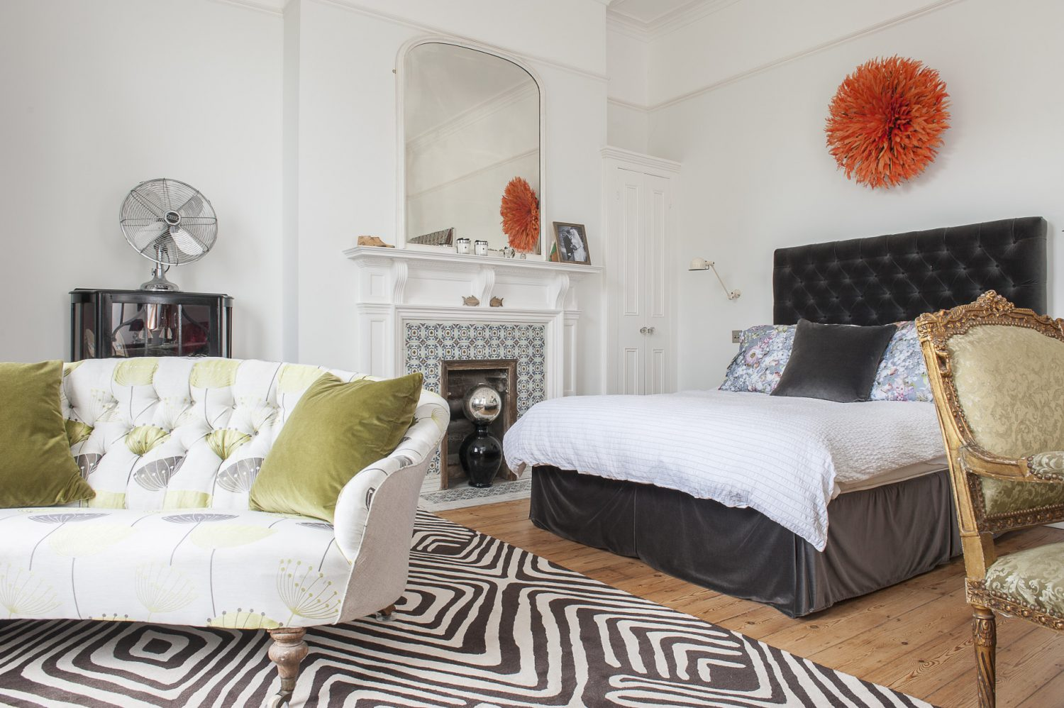 The fireplace in the couple's master bedroom has been stripped of paint and returned to its former glory. The velvet button backed headboard and bed come from sofa.com and the Cameroonian tribal headdress from Sideshow Interiors in St Leonards.
