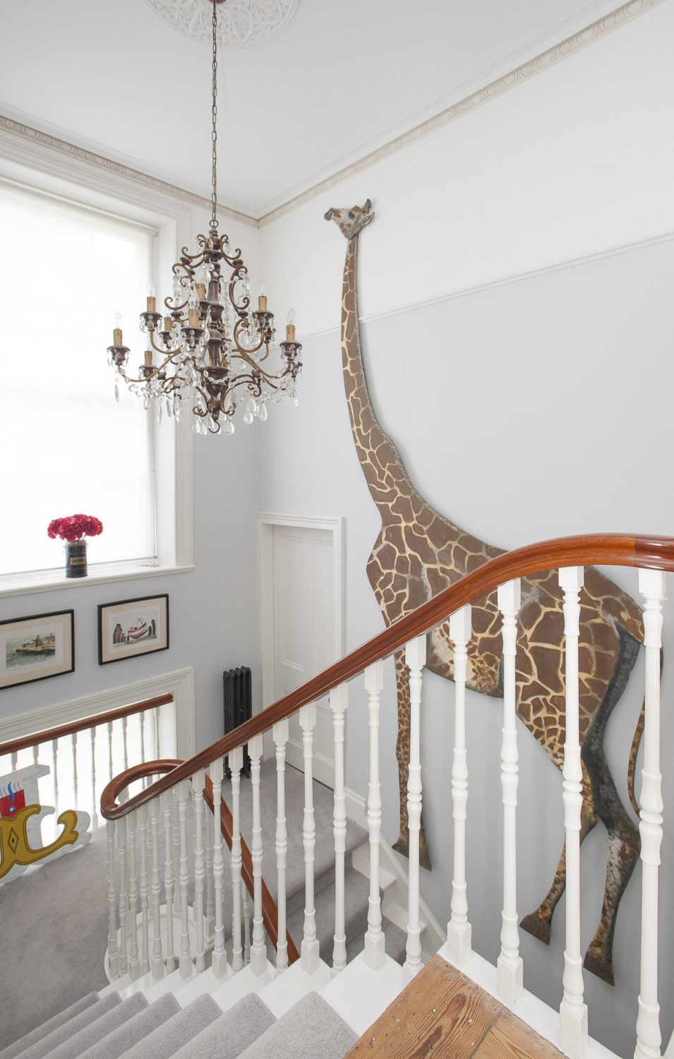 A full sized cut-out of a giraffe reaches virtually from the ground to first floor