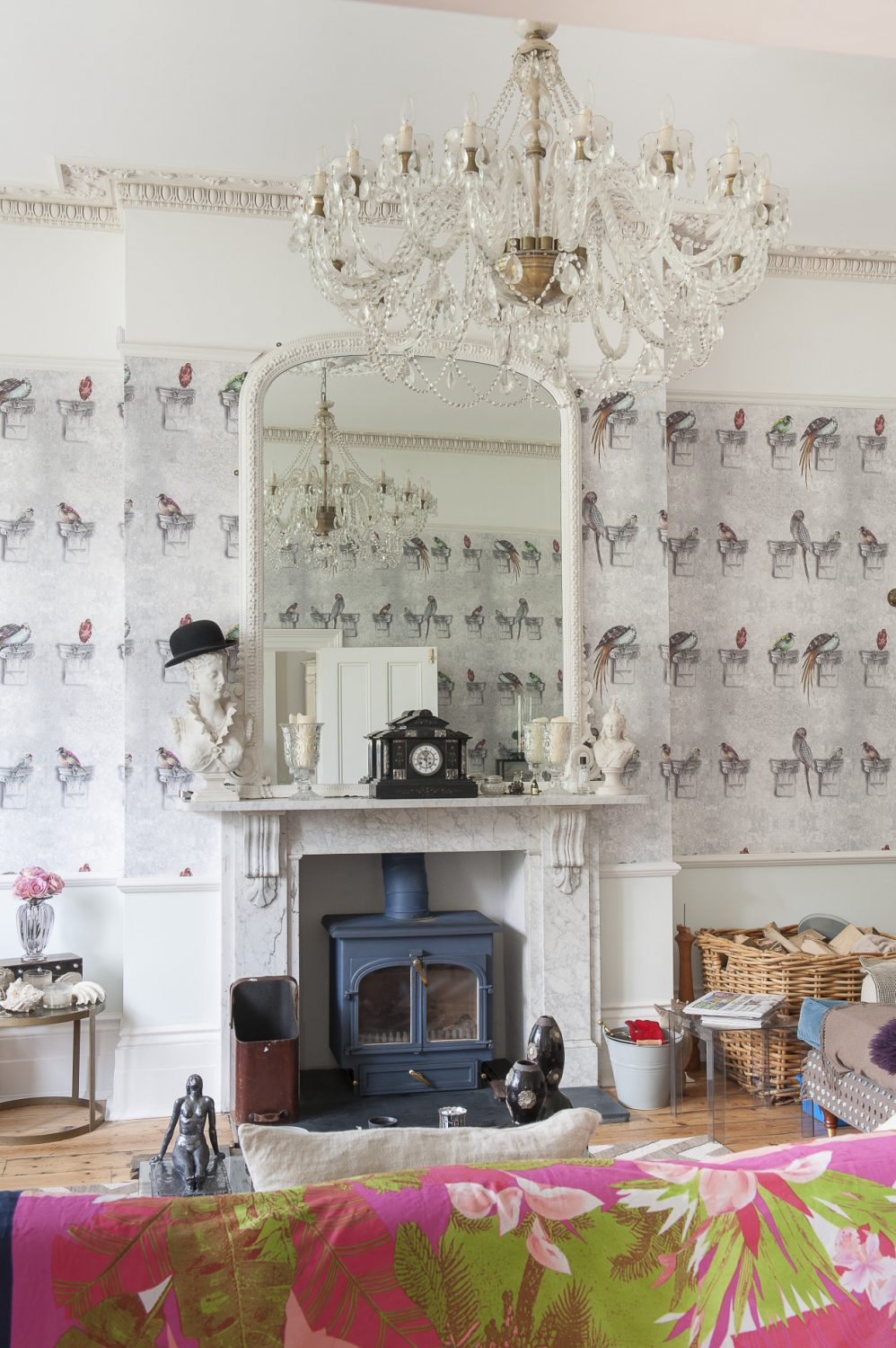 Lighting is a major feature of each room. The huge chandelier in the drawing room was a Bexhill find and the fun parrot wallpaper is by Louise Body