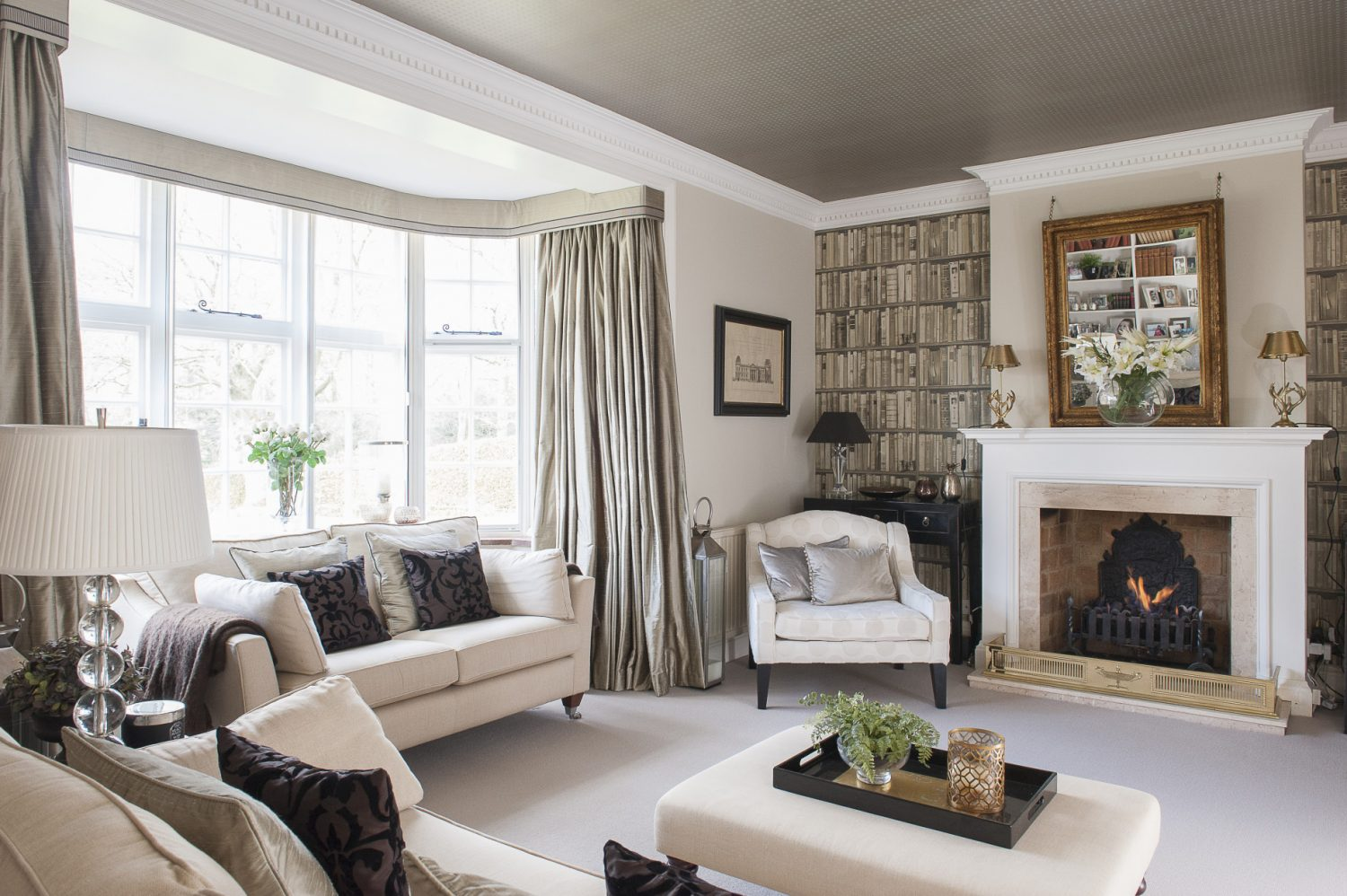 On either side of the fireplace, the alcoves are papered with Andrew Martin's faux books and over the mantelpiece, Victoria has hung a gilt mirror from a heavy antique chain that, cleverly, tilts the looking glass in a downward direction, reflecting the room