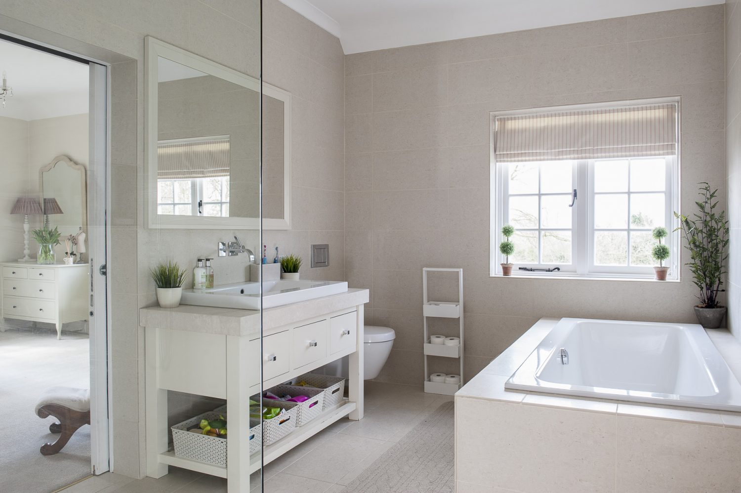 The children's Jack & Jill bathroom has sliding doors to leave maximum space for washing. Pale travertine tiles cover the floor and walls and the room was tanked to cope with splashes from the huge bath and walk-in shower