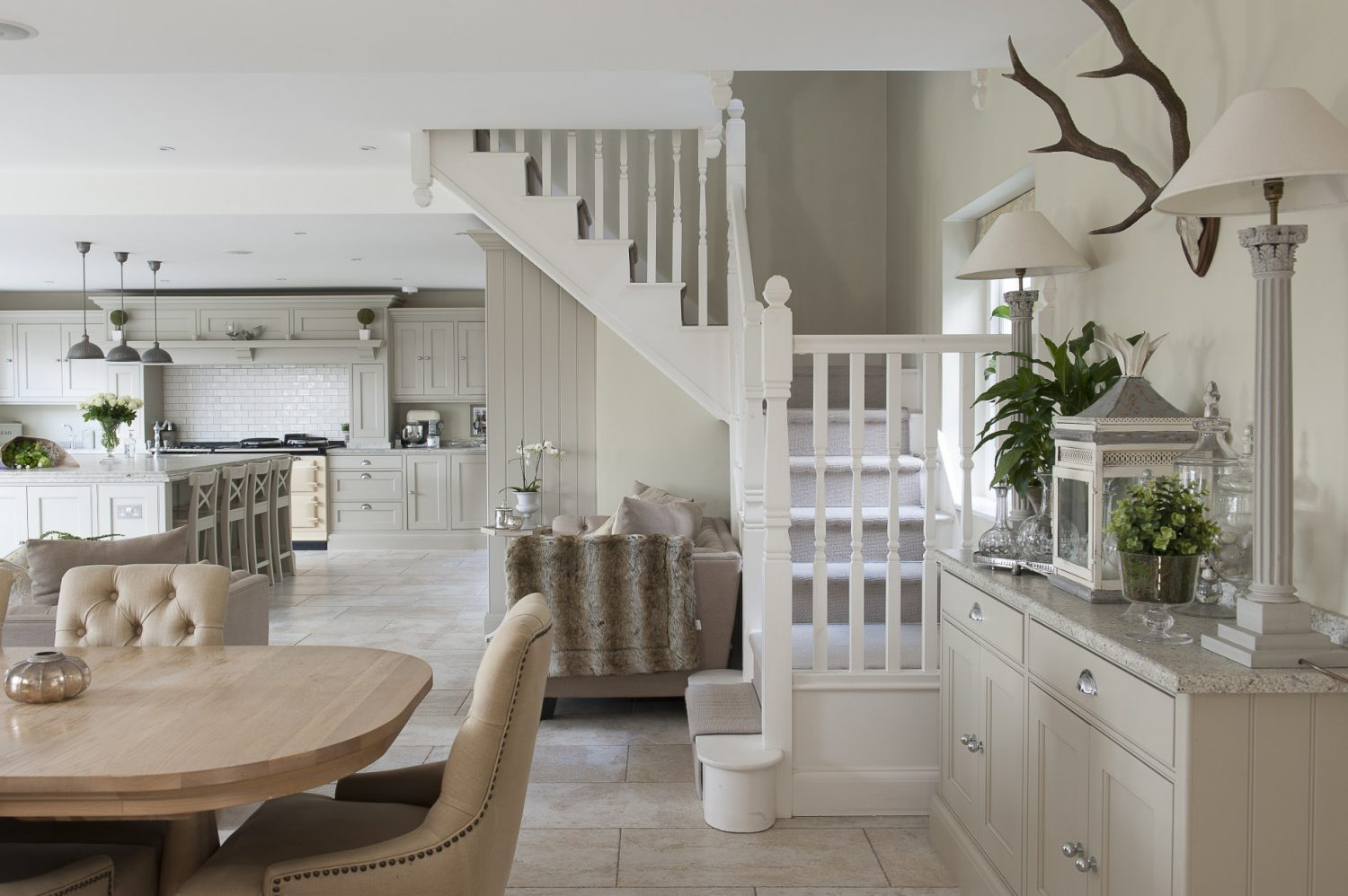 Although the room is huge, it's cleverly divided up into distinct areas, so that beyond the working part, a pair of linen-covered sofas provide a sociable spot for family and friends to lounge and chat while food is being prepared