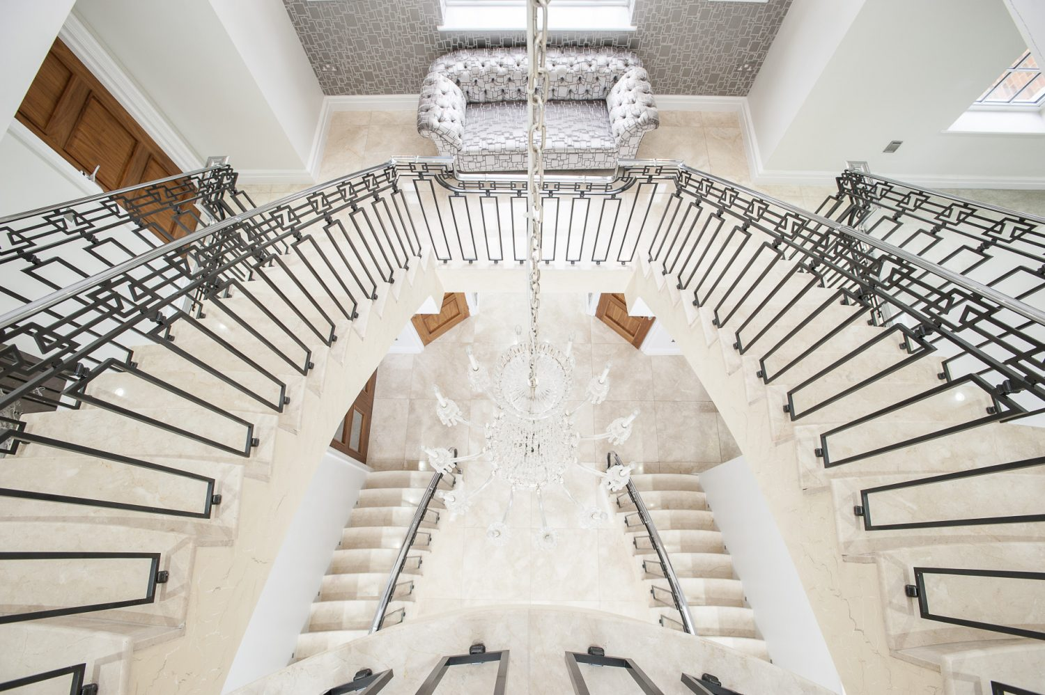 The vast and delicate horseshoe staircase sweeps up three floors creating a huge, soaring marble and crystal atrium