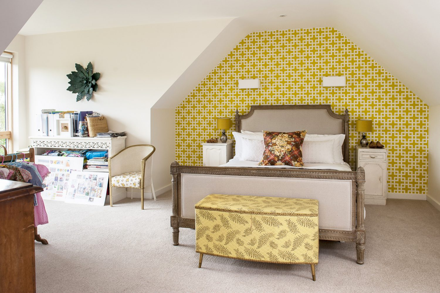 The guest room occupies a vaulted space at the top of the house in which Jenny has appropriated a place by the window to serve as her office. The wall over the Loaf bed is papered in Clarke & Clarke 'Lattice' next to which stands an unusual gilt Lloyd Loom chair