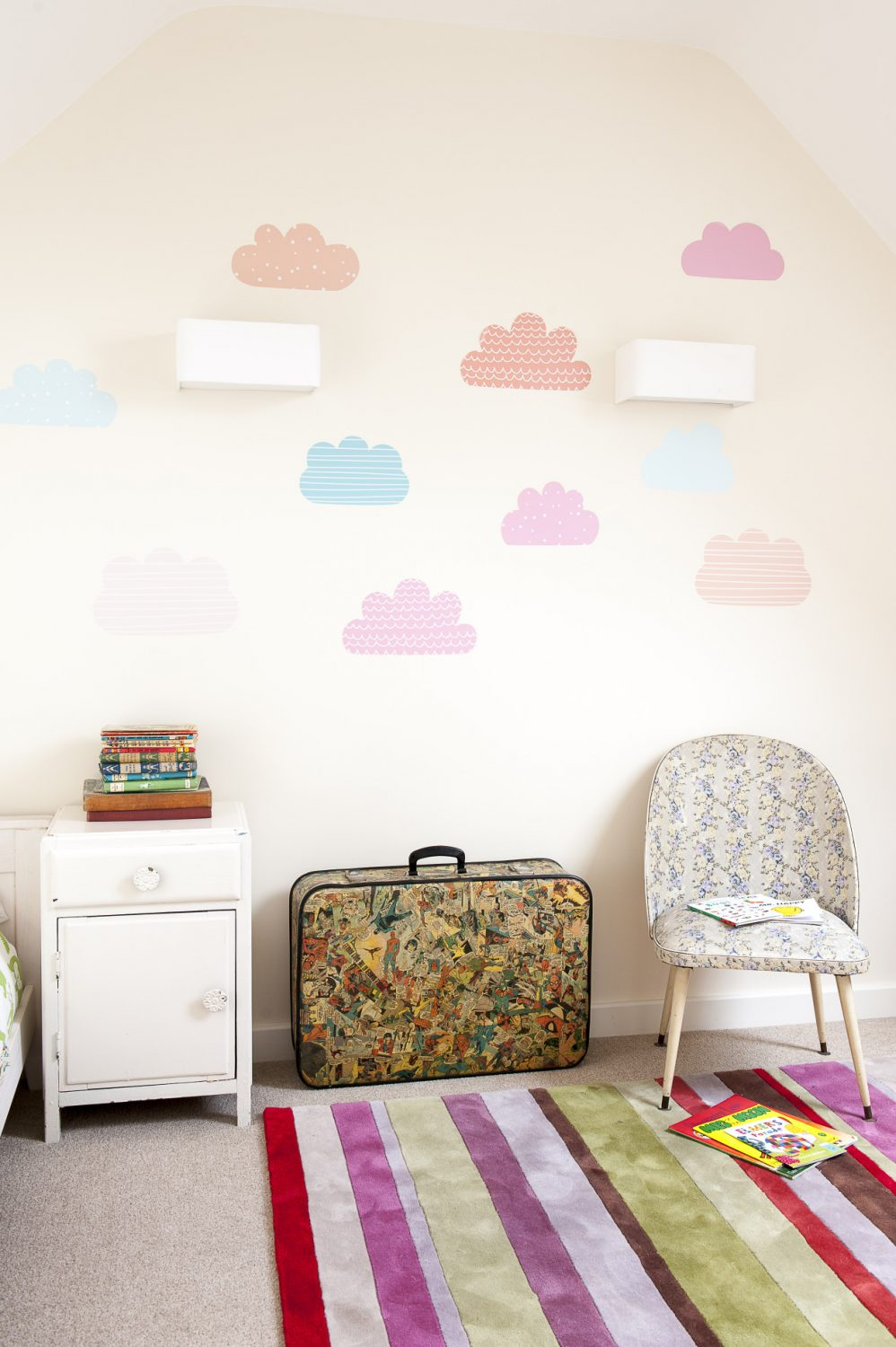 Pastel paper clouds float across one wall of the children's guest room at the top of the house