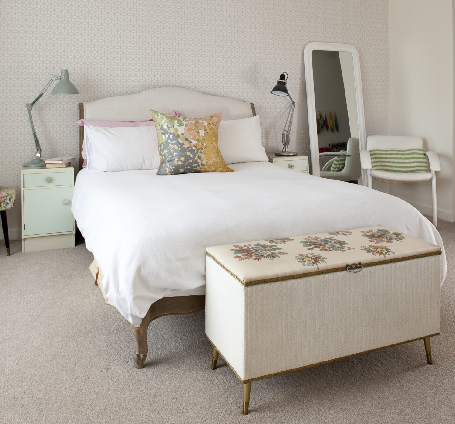 The master bedroom adheres to a palette of delicate whites and pastels, the trellis wallpaper by Harlequin. Each side of the Loaf bed are matching 60s cabinets on which stand two Anglepoises – one 60s and the other contemporary. Beside the bed stands an elegant, 60s steel-framed, white leather chair