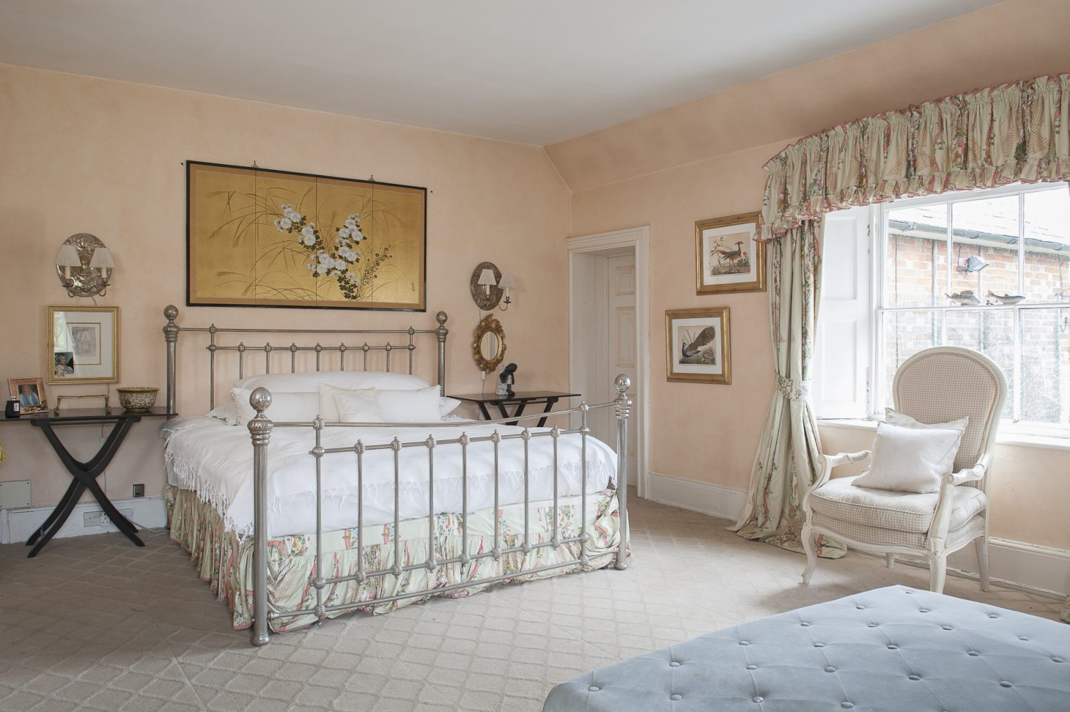 Peachy cream paintwork offsets oriental paintings of birds and flowers, while light dances off the metal bedstead and gilt light sconces. A marble fireplace at the foot of the bed framed on either side by heavy, patterned curtains, gives the room a sense of grandeur as well as softness