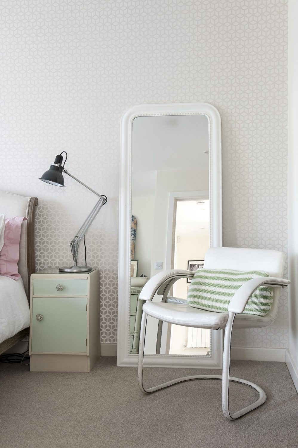 Beside the bed stands an elegant, 60s steel-framed, white leather chair